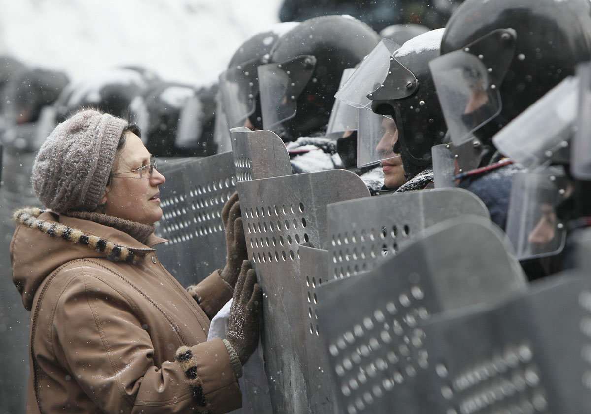 A woman addresses Ukrainian Interior Ministry members who lined up during clashes with pro-European protesters in Kiev