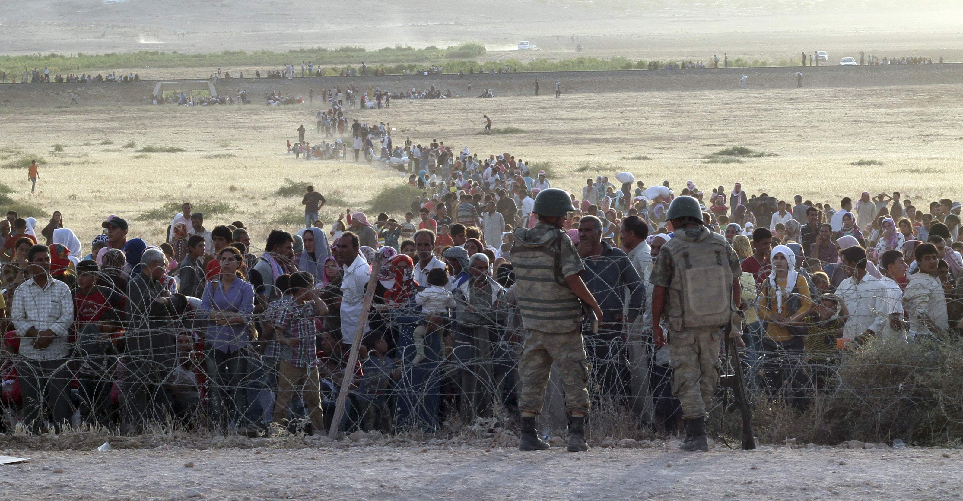 Turkish soldiers stand guard as Syrians wait behind the border fences near the southeastern town of Suruc in Sanliurfa province