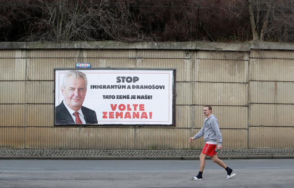 A man walks past a poster promoting the incumbent president Milos Zeman in Prague