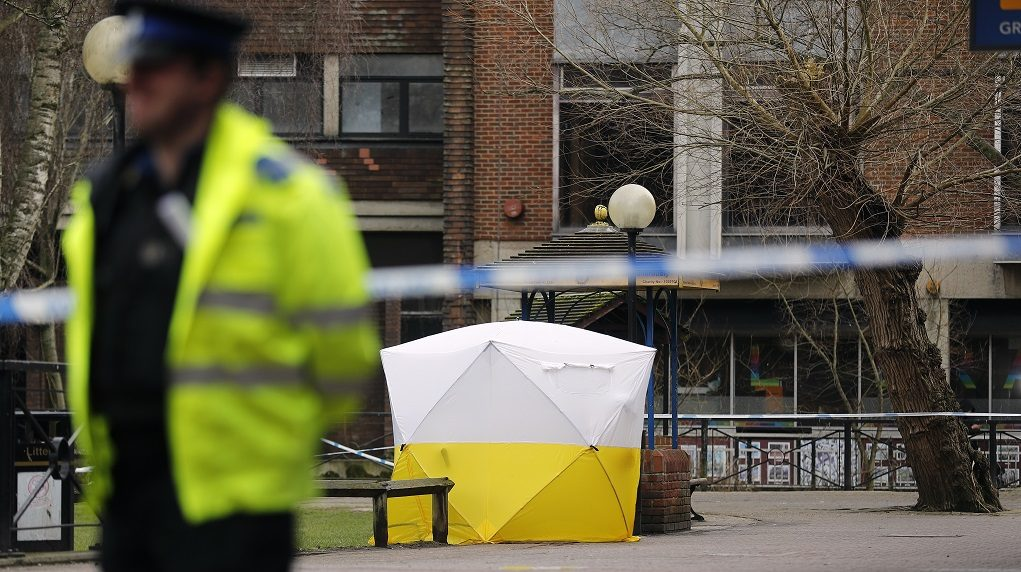"Police officer secures the area as a police tent covers the the spot in Salisbury, England, Tuesday, March 6, 2018, where former Russian spy double agent Sergei Skripal and his companion were found critically ill Sunday following exposure to an ""unknown substance"".  66-year old Skripal, and unidentified woman companion are being treated in hospital, after they were found unconscious on the park bench.(AP Photo/Frank Augstein)"